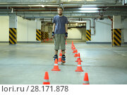 Купить «Roller skater stands near orange cones in empty underground parking», фото № 28171878, снято 22 октября 2015 г. (c) Losevsky Pavel / Фотобанк Лори