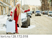 Купить «Young woman with trolley bag tries to catch cat on snow-covered road», фото № 28172018, снято 15 января 2016 г. (c) Losevsky Pavel / Фотобанк Лори