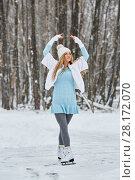 Купить «Young woman poses standing on skates at outdoor skate rink in winter park», фото № 28172070, снято 19 января 2016 г. (c) Losevsky Pavel / Фотобанк Лори
