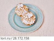 Купить «Closeup two cupcakes with white cream on plate on table», фото № 28172158, снято 19 января 2016 г. (c) Losevsky Pavel / Фотобанк Лори