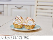 Купить «Closeup two cupcakes with white cream on plate on table», фото № 28172162, снято 19 января 2016 г. (c) Losevsky Pavel / Фотобанк Лори