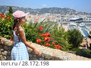 Купить «Girl standing near stone wall and red flowers and looks at Cannes, France», фото № 28172198, снято 29 июля 2016 г. (c) Losevsky Pavel / Фотобанк Лори