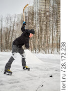 Купить «Alone hockey player going to slash puck at outdoor skating rink», фото № 28172238, снято 21 января 2016 г. (c) Losevsky Pavel / Фотобанк Лори