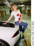 Купить «Young smiling woman poses sitting on trunk of modern white car at underground parking», фото № 28172362, снято 2 июня 2016 г. (c) Losevsky Pavel / Фотобанк Лори