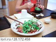 Купить «Green salad is one white plate on table in cafe, femake hands out of focus», фото № 28172458, снято 2 ноября 2015 г. (c) Losevsky Pavel / Фотобанк Лори