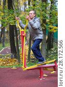 Купить «Elderly man is engaged on sport simulator in autumn park with fallen leaves», фото № 28172566, снято 6 октября 2016 г. (c) Losevsky Pavel / Фотобанк Лори