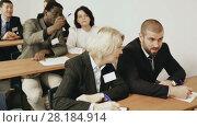 Купить «International group of business people listening to presentation at tables in boardroom», видеоролик № 28184914, снято 26 февраля 2018 г. (c) Яков Филимонов / Фотобанк Лори