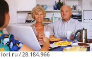 Купить «Young woman showing elderly couple something interesting on laptop over cup of tea», видеоролик № 28184966, снято 7 сентября 2017 г. (c) Яков Филимонов / Фотобанк Лори
