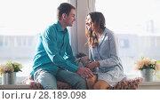 Купить «Young and attractive guy and girl sitting on the windowsill and kissing, guy giving girl a plush Bunny», фото № 28189098, снято 27 апреля 2018 г. (c) Константин Шишкин / Фотобанк Лори