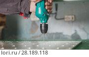 Купить «Industrial drilling machine - worker makes holes in metal», фото № 28189118, снято 21 июля 2019 г. (c) Константин Шишкин / Фотобанк Лори