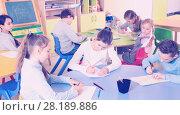 Купить «Portrait of young teacher woman at lesson with diligent school kids», фото № 28189886, снято 28 января 2018 г. (c) Яков Филимонов / Фотобанк Лори
