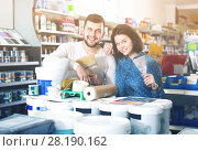 Купить «Young couple demonstrating tools for house renovating in paint store», фото № 28190162, снято 9 марта 2017 г. (c) Яков Филимонов / Фотобанк Лори