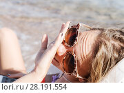 Купить «A young tanned woman looks at her nail-manicure and laughs at the smartphone through sunglasses on a deckchair. The concept of a relaxed lifestyle», фото № 28191554, снято 9 октября 2016 г. (c) Tetiana Chugunova / Фотобанк Лори