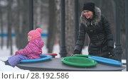 Купить «Together mother with cute little daughter playing in the winter park», видеоролик № 28192586, снято 24 апреля 2018 г. (c) Константин Шишкин / Фотобанк Лори