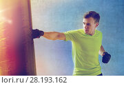Купить «young man in gloves boxing with punching bag», фото № 28193162, снято 29 июня 2014 г. (c) Syda Productions / Фотобанк Лори