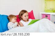 Купить «little girls or sisters reading book in bed», фото № 28193230, снято 15 октября 2017 г. (c) Syda Productions / Фотобанк Лори