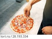 Купить «cook adding onion to salami pizza at pizzeria», фото № 28193334, снято 17 февраля 2017 г. (c) Syda Productions / Фотобанк Лори