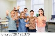 Купить «happy students waving hands at school», фото № 28193370, снято 9 января 2016 г. (c) Syda Productions / Фотобанк Лори