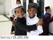 Купить «Two young Cambodian Cham Muslim boy smiling in Kampong Cham mosque, Cambodia, South East Asia, Asia.», фото № 28200346, снято 24 ноября 2017 г. (c) age Fotostock / Фотобанк Лори
