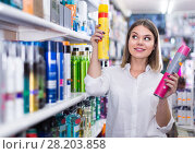 Купить «smiling young woman choosing haircare products at store», фото № 28203858, снято 31 января 2018 г. (c) Яков Филимонов / Фотобанк Лори