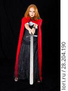 Купить «Halloween girl wearing in black long gown and red robe brandishing twohanded sword, on a dark background», фото № 28204190, снято 6 июля 2017 г. (c) Сергей Дубров / Фотобанк Лори