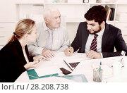 Купить «Managers are writing financial reports and discussing with mature boss», фото № 28208738, снято 27 июня 2017 г. (c) Яков Филимонов / Фотобанк Лори