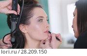 Купить «Make up artist doing professional make-up lips for attractive young model», видеоролик № 28209150, снято 17 августа 2018 г. (c) Константин Шишкин / Фотобанк Лори