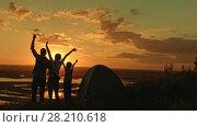 Купить «Young happy healthy family - father, mom and son in camping - stands on high hill at summer sunset and have happy, silhouette», видеоролик № 28210618, снято 24 апреля 2018 г. (c) Константин Шишкин / Фотобанк Лори