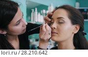 Professional makeup artist doing make-up with black eyeliner. Стоковое видео, видеограф Константин Шишкин / Фотобанк Лори