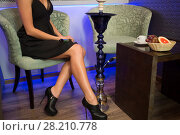 Купить «Beautiful girl in black dress sitting in the hookah room», фото № 28210778, снято 22 апреля 2015 г. (c) Losevsky Pavel / Фотобанк Лори