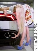 Купить «Young blonde woman in flowery dress touches exhaust pipe of modern white car at underground parking», фото № 28210782, снято 2 июня 2016 г. (c) Losevsky Pavel / Фотобанк Лори