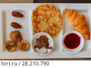 Купить «Dates, figs, pancake, chocolate, sweet sauce and croissant at compartmental dish», фото № 28210790, снято 4 августа 2016 г. (c) Losevsky Pavel / Фотобанк Лори