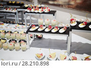Купить «Rows of snacks and drinks on banquet table in restaurant», фото № 28210898, снято 6 июня 2016 г. (c) Losevsky Pavel / Фотобанк Лори