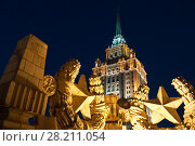 Tower with spire on Ukraine hotel (Stalin skyscraper) and concrete soviet stars at night in Moscow. Стоковое фото, фотограф Losevsky Pavel / Фотобанк Лори