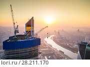 Купить «Sunrise in the foggy day over Moscow. Top view from building under construction», фото № 28211170, снято 20 апреля 2014 г. (c) Losevsky Pavel / Фотобанк Лори
