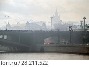 Купить «Patriarchal bridge with lanterns in fog and silhouette of big building in Moscow», фото № 28211522, снято 3 апреля 2016 г. (c) Losevsky Pavel / Фотобанк Лори