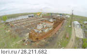 Купить «SAMARA - MAY 10, 2015: Wharf with unfinished vessel on shore of Volga river at spring cloudy day. Aerial view video frame», фото № 28211682, снято 10 мая 2015 г. (c) Losevsky Pavel / Фотобанк Лори