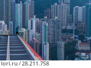 Купить «Man on roof shoots skyscrapers and tall residential buildings in Hong Kong, China, view from China Merchants Tower», фото № 28211758, снято 31 августа 2015 г. (c) Losevsky Pavel / Фотобанк Лори