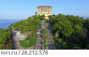 Купить «ALANIA - AUG 16, 2015: Alley to edifice of Hotel Utopia World on top of hill near sea at summer sunny day. Aerial view videoframe. Utopia World is a 5-star hotel.», фото № 28212578, снято 16 августа 2015 г. (c) Losevsky Pavel / Фотобанк Лори