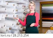 Купить «Female seller 55-60 years old is demonstrating fabrics», фото № 28213254, снято 15 февраля 2017 г. (c) Яков Филимонов / Фотобанк Лори