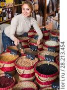 Купить «woman taking dried beans», фото № 28213454, снято 15 ноября 2018 г. (c) Яков Филимонов / Фотобанк Лори