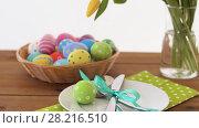 Купить «easter eggs in basket and flowers on served table», видеоролик № 28216510, снято 15 марта 2018 г. (c) Syda Productions / Фотобанк Лори