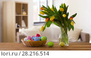 Купить «colored easter eggs in basket and flowers at home», видеоролик № 28216514, снято 15 марта 2018 г. (c) Syda Productions / Фотобанк Лори