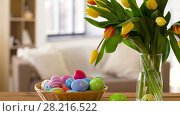 Купить «colored easter eggs in basket and flowers at home», видеоролик № 28216522, снято 15 марта 2018 г. (c) Syda Productions / Фотобанк Лори