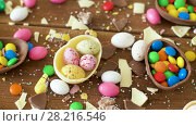 Купить «chocolate easter eggs and drop candies on table», видеоролик № 28216546, снято 23 марта 2018 г. (c) Syda Productions / Фотобанк Лори