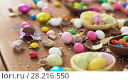 Купить «chocolate easter eggs and drop candies on table», видеоролик № 28216550, снято 16 марта 2018 г. (c) Syda Productions / Фотобанк Лори