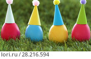 Купить «easter eggs in party caps on artificial grass», видеоролик № 28216594, снято 15 марта 2018 г. (c) Syda Productions / Фотобанк Лори