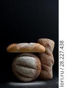 Купить «Freshly baked different breads on a black background.», фото № 28227438, снято 21 марта 2018 г. (c) Olesya Tseytlin / Фотобанк Лори