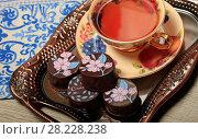 Купить «Конфеты с шоколадной глазурью и чай в красивой чашке», фото № 28228238, снято 22 марта 2018 г. (c) Яна Королёва / Фотобанк Лори