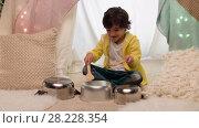 Купить «boy with pots playing music in kids tent at home», видеоролик № 28228354, снято 23 февраля 2018 г. (c) Syda Productions / Фотобанк Лори